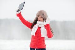 冬天裘皮帽的妇女有户外片剂个人计算机的 库存图片