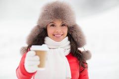 冬天裘皮帽的愉快的妇女用咖啡户外 免版税库存图片