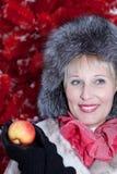 冬天裘皮帽的美丽的妇女在红色背景圣诞树 免版税库存图片