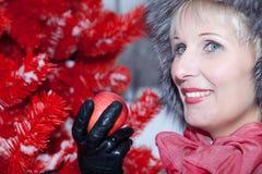 冬天裘皮帽的美丽的妇女在红色背景圣诞树 免版税图库摄影