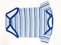 冬天说谎在地板上的婴孩衣裳 免版税库存图片