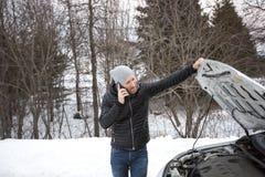 冬天路的人在汽车附近叫电话 图库摄影