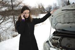 冬天路的女孩在汽车附近叫电话 免版税库存图片
