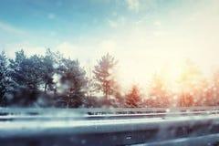 冬天路通过多雪的领域和森林 免版税库存照片