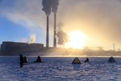 冬天钓鱼,人的激情,渔夫抓在一条冻河的鱼以工厂管子为背景在日落 免版税库存照片