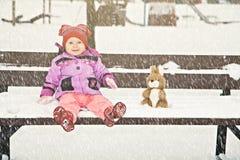 冬天长凳的婴孩与她的玩具 免版税库存图片