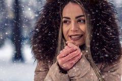 冬天雪天打击的愉快的妇女在她冷的手上 免版税库存照片