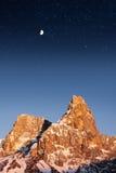 冬天雪山日落月亮满天星斗的天空 免版税库存照片