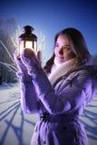 冬天雪的女孩与圣诞节灯笼 免版税库存图片