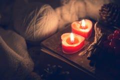 冬天静物画用花楸浆果、被编织的毛线衣和两红色蜡烛在一本旧书作为爱的一起标志和 库存照片