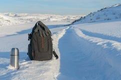 冬天风景、热水瓶和背包在雪 免版税库存照片