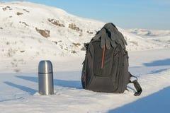 冬天风景、热水瓶和背包在雪 免版税库存图片