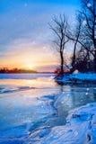 冬天风景全景;在一条冻河的河岸的日落; 免版税库存照片