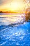冬天风景全景;在一条冻河的河岸的日落; 库存图片