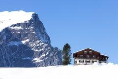 冬天风景在奥地利阿尔卑斯,在雪的木瑞士山中的牧人小屋 免版税图库摄影