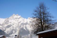冬天风景清早在有雪、木大厦、蓝天和拷贝空间的奥地利 免版税图库摄影