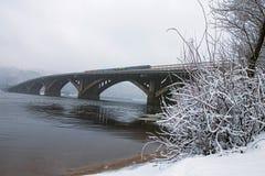 冬天风景照片 横跨Dnipro河的Metrosubway桥梁在有雾的早晨 雪盖树` s早午餐和地面 库存照片