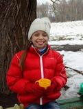 冬天风景的背景的逗人喜爱的微笑的女孩 库存照片
