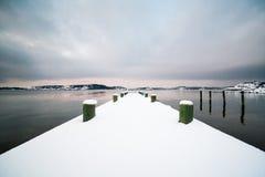 冬天风景,在码头的雪由海洋 免版税库存照片