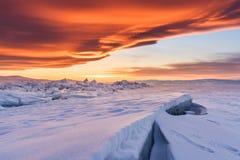 冬天风景,破裂的结冰的湖地面报道在日落的雪用美丽的天空在贝加尔湖在伊尔库次克,俄罗斯 库存照片
