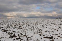 冬天风景-用第一下落的雪包括的耕地在一个晴天 图库摄影