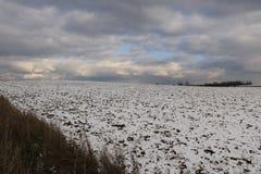冬天风景-用第一下落的雪包括的耕地在一个晴天 免版税库存图片