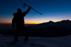 冬天高涨:人在看日落的一个多雪的土坎站立 库存照片