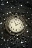 冬天魔术 古色古香的poÑ  ket手表和落雪 免版税库存图片