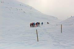 冬天,与远足者的积雪的山 免版税库存图片