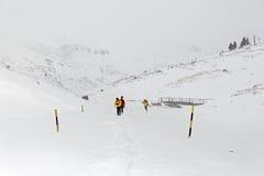 冬天,与远足者的积雪的山 库存图片
