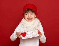 冬天,孩子,华伦泰爱概念-帽子的愉快的女孩有箱子礼物展示心脏羊毛的在红色戏弄 库存照片