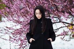 冬天,穿温暖的外套的年轻美丽的深色的妇女的春天画象 花和雪秀丽时尚概念 库存照片