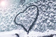 冬天,雪,冷 在汽车玻璃被绘的心脏 那里定调子 库存照片