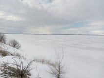 冬天,雪,阴云密布,在冰下的河,冰渔,天空覆盖,白色天际,白色干草原 免版税库存图片
