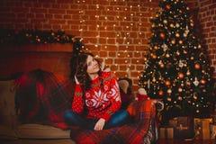 冬天, xmas画象:少妇在红色温暖的羊毛羊毛衫、摆在室内近的圣诞树的手套和帽子穿戴了 库存图片