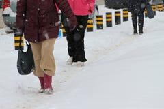 冬天 人们在一条非常多雪的边路和路走 人们在一条冰冷的路,冰冷的边路跨步 未清理的街道和路 图库摄影