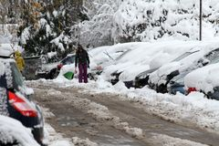 冬天 冰 雪 人们在通过在未清理的冰冷的街道上的多雪的汽车在以后大雪的一条多雪的冰冷的路艰苦走 Unclea 免版税库存图片