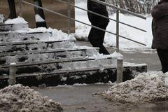 冬天 台阶 人们在走非常多雪的台阶到地下过道 人们在跨步冰冷的台阶,溜滑台阶 免版税图库摄影