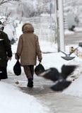 冬天 在一条非常多雪的边路的人步行 在一条雪离群路的人步 冰冷的边路 在边路的冰 免版税库存照片