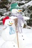 冬天-在爱的雪人夫妇在与帽子的一个多雪的风景 免版税库存照片
