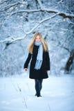 冬天 女孩走的多雪的森林和微笑对照相机 巨大心情 库存照片