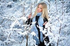 冬天 女孩走的多雪的森林和微笑对照相机 巨大心情 免版税库存照片