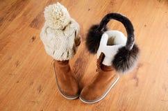 冬天靴子、帽子和毛皮耳机在水平的地板上 库存图片