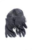 冬天黑色编织手套和温暖的帽子在雪 库存图片