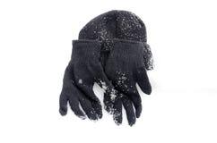 冬天黑色编织手套和温暖的帽子在雪 免版税库存照片