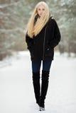 冬天画象:年轻白肤金发的妇女在一件温暖的羊毛摆在外面在一个多雪的公园的夹克蓝色牛仔裤长的起动穿戴了 免版税库存图片