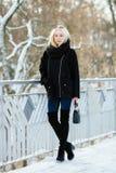 冬天画象:年轻白肤金发的妇女在一件温暖的羊毛摆在外面在一个多雪的城市公园的夹克蓝色牛仔裤长的起动穿戴了 免版税库存图片