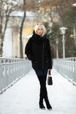 冬天画象:年轻白肤金发的妇女在一件温暖的羊毛摆在外面在一个多雪的城市公园的夹克蓝色牛仔裤长的起动穿戴了 免版税库存照片