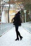 冬天画象:年轻白肤金发的妇女在一件温暖的羊毛摆在外面在一个多雪的城市公园的夹克蓝色牛仔裤长的起动穿戴了 库存照片