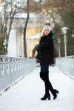 冬天画象:年轻白肤金发的妇女在一件温暖的羊毛摆在外面在一个多雪的城市公园的夹克蓝色牛仔裤长的起动穿戴了 图库摄影